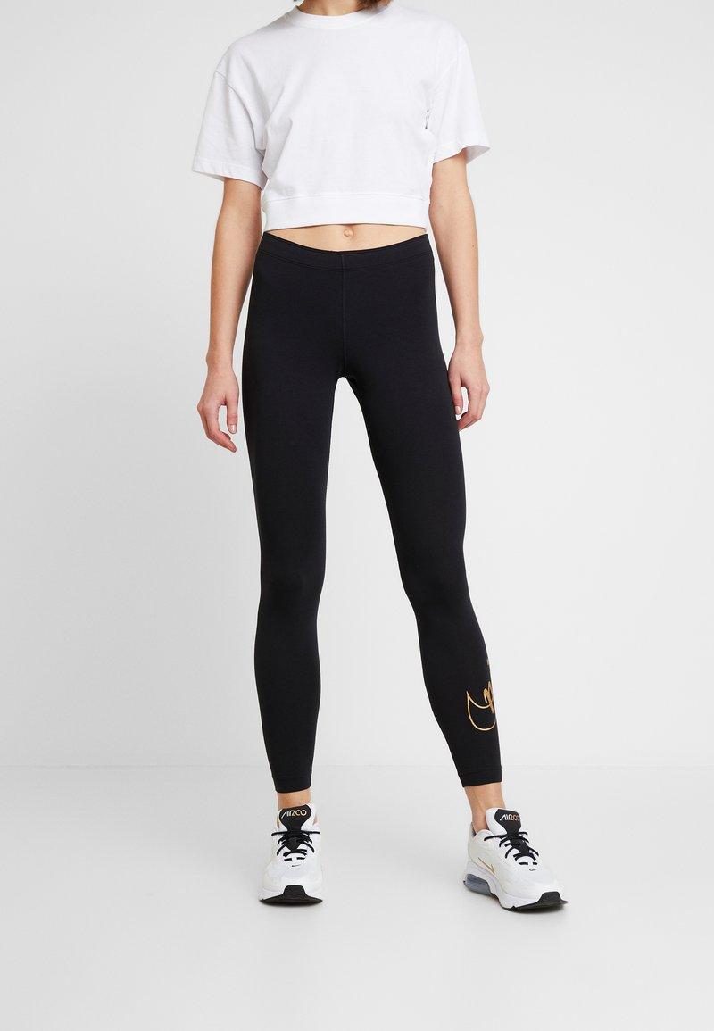 Nike Sportswear - GLITTER - Leggings - black/gold