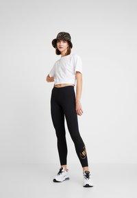 Nike Sportswear - GLITTER - Leggings - black/gold - 1
