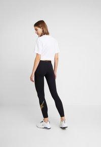 Nike Sportswear - GLITTER - Leggings - black/gold - 2