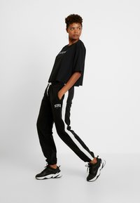 Nike Sportswear - Tracksuit bottoms - black/sail - 2