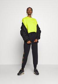 Nike Sportswear - PEACE PACK PANT - Joggebukse - black/green spark - 1