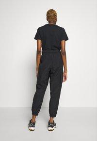 Nike Sportswear - W NSW ICN CLSH PANT WVN - Tracksuit bottoms - black/fire pink - 2