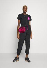 Nike Sportswear - W NSW ICN CLSH PANT WVN - Tracksuit bottoms - black/fire pink - 1