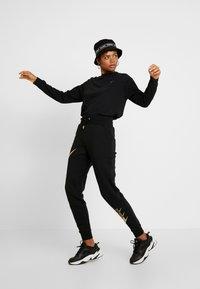 Nike Sportswear - Long sleeved top - black/metallic gold - 1