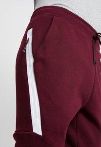 Nike Sportswear - TECH - Spodnie treningowe - night maroon - 5