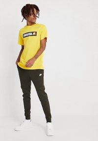 Nike Sportswear - TECH - Spodnie treningowe - sequoia/white - 1