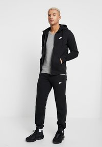 Nike Sportswear - CLUB CUFFED PANT - Tracksuit bottoms - black/white