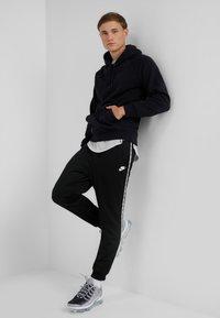 Nike Sportswear - POLY - Pantalon de survêtement - black/white - 1