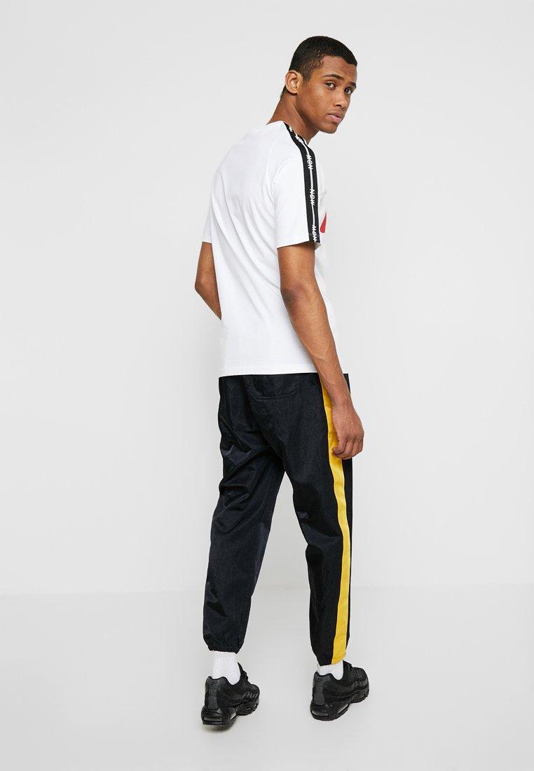 Nike Sportswear - PANT - Tracksuit bottoms - black/yellow ochre