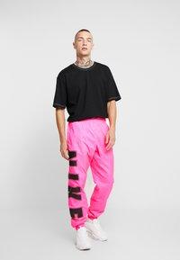 Nike Sportswear - WOVEN  - Verryttelyhousut - hyper pink/black - 1