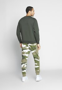 Nike Sportswear - CLUB CAMO - Pantalon de survêtement - medium olive/summit white - 2