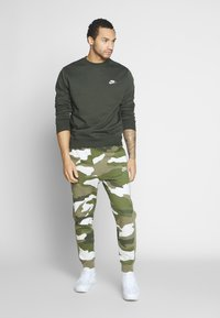 Nike Sportswear - CLUB CAMO - Pantalon de survêtement - medium olive/summit white - 1