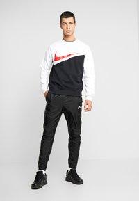 Nike Sportswear - PANT PATCH - Tracksuit bottoms - black - 1