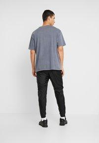 Nike Sportswear - PANT PATCH - Tracksuit bottoms - black - 2