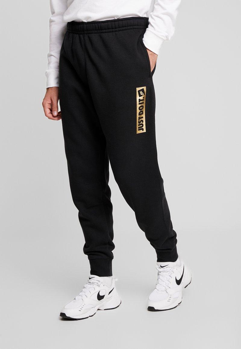 Nike Sportswear - METALLIC - Tracksuit bottoms - black