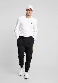 Nike Sportswear - METALLIC - Pantalones deportivos - black - 1