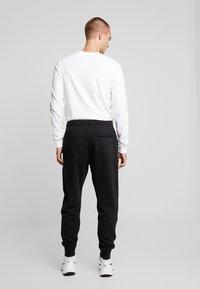 Nike Sportswear - METALLIC - Tracksuit bottoms - black - 2