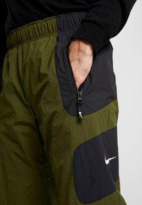 Nike Sportswear - RE-ISSUE PANT  - Trainingsbroek - black/legion green/white - 5