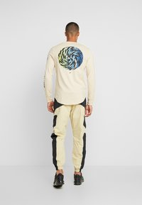 Nike Sportswear - RE-ISSUE PANT  - Pantalones deportivos - black/team gold - 2
