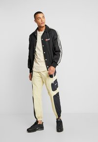 Nike Sportswear - RE-ISSUE - Tracksuit bottoms - black/team gold - 1