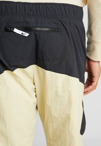 Nike Sportswear - RE-ISSUE - Tracksuit bottoms - black/team gold - 3