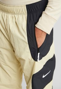 Nike Sportswear - RE-ISSUE - Tracksuit bottoms - black/team gold - 5