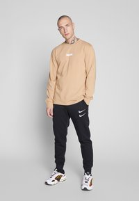 Nike Sportswear - M NSW PANT FT - Tracksuit bottoms - black/white - 1