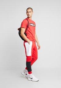 Nike Sportswear - M NSW NIKE AIR PANT FLC - Pantalon de survêtement - university red/white/black - 1