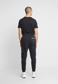 Nike Sportswear - M NSW NIKE AIR PANT FLC - Pantalones deportivos - black/university red - 3