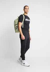 Nike Sportswear - M NSW NIKE AIR PANT FLC - Pantalones deportivos - black/university red - 1