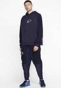 Nike Sportswear - Tracksuit bottoms - blackened blue/mystic green/black - 1