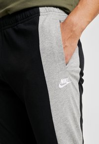 Nike Sportswear - Tracksuit bottoms - black/grey heather - 4