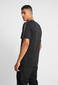 Nike Sportswear - REPEAT TEE - T-shirt med print - black/metallic gold - 2