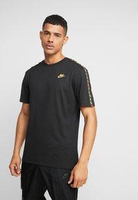Nike Sportswear - REPEAT TEE - T-shirt med print - black/metallic gold - 0