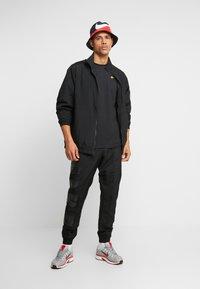Nike Sportswear - REPEAT TEE - T-shirt med print - black/metallic gold - 1