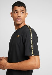 Nike Sportswear - REPEAT TEE - T-shirt med print - black/metallic gold - 4