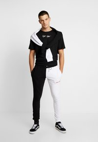 Night Addict - FERN - Pantalones deportivos - black/ white - 1