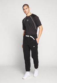 Nike SB - NOVELTY PANT - Verryttelyhousut - black/(sail) - 1