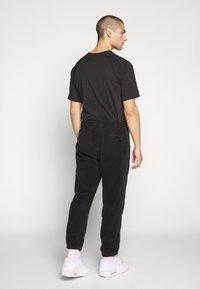 Nike SB - NOVELTY PANT - Verryttelyhousut - black/(sail) - 2