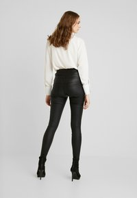 ONLY - ONLCORAL CORSAGE ROCK COATED - Pantalones - black - 2