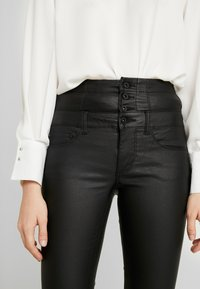 ONLY - ONLCORAL CORSAGE ROCK COATED - Pantalones - black - 5