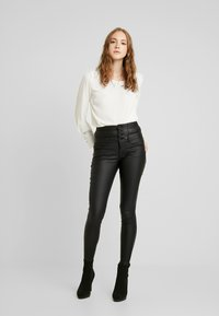 ONLY - ONLCORAL CORSAGE ROCK COATED - Pantalones - black - 1