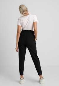ONLY Petite - ONLPOPTRASH CLASSI PINSTRIPE FRILL - Trousers - black - 2