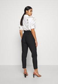 ONLY Petite - ONLPOPTRASH CLASSI PINSTRIPE FRILL - Pantalones - black - 2