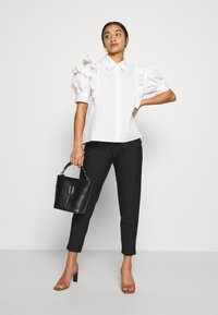 ONLY Petite - ONLPOPTRASH CLASSI PINSTRIPE FRILL - Pantalones - black - 1