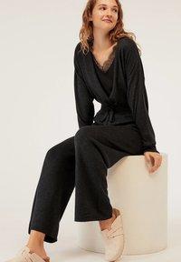OYSHO - MIT WEITEM BEIN - Trousers - black - 4
