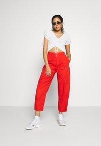 Pepe Jeans - DUA LIPA x PEPE JEANS - Spodnie materiałowe - bright orange - 1