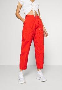 Pepe Jeans - DUA LIPA x PEPE JEANS - Spodnie materiałowe - bright orange - 0