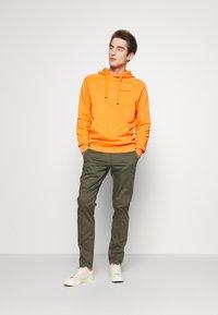 Peak Performance Urban - URBAN HOODIE - Jersey con capucha - orange dune - 1