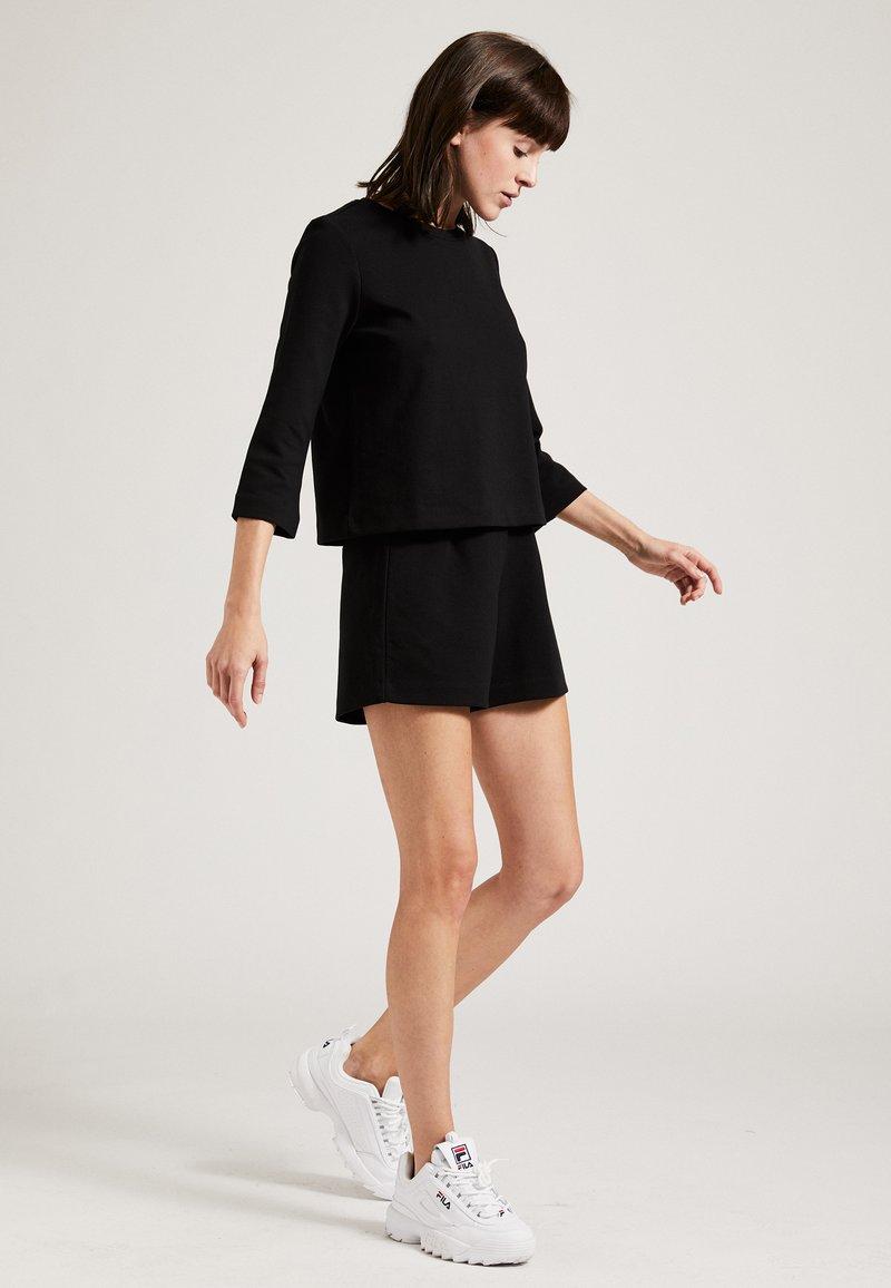Phyne - Shorts - black
